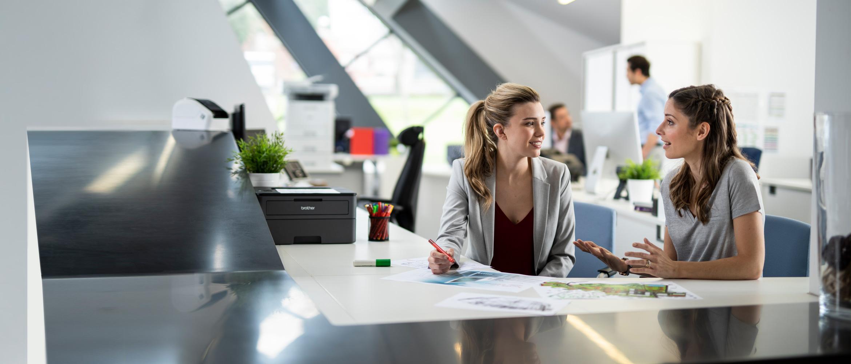 Dvije žene sjede u punom uredu za stolom i razgovaraju, muškarci u pozadini, pisači, olovke, dokumenti
