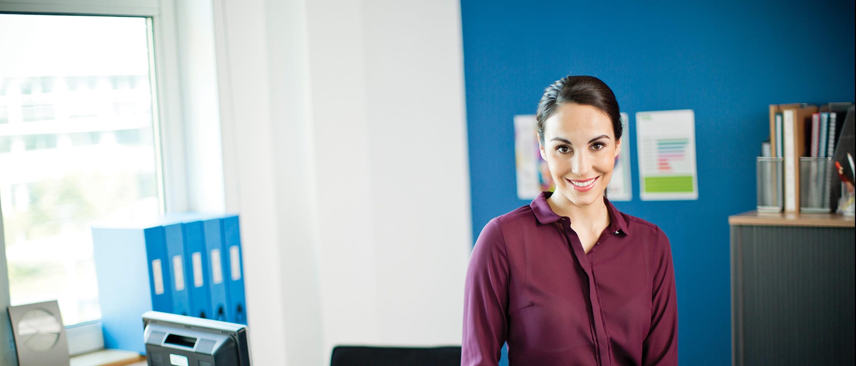 Žena u uredu s raznim uredskim predmetima označenim oko sebe