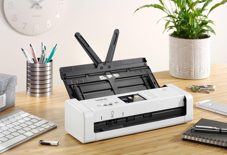 otvoren kompaktni skener dokumenata Brother ADS-1700W na drvenom stolu s biljkom i tipkovnicom
