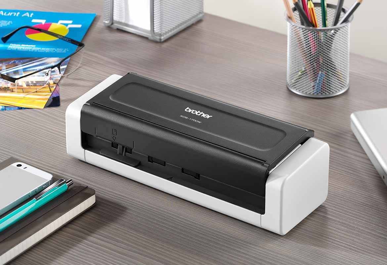 zatvoren kompaktni skener dokumenata Brother ADS-1700W na sivom stolu