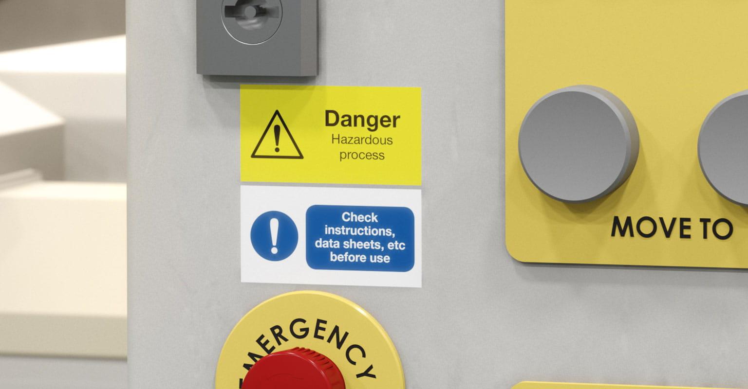 Dvije naljepnice na upravljačkoj ploči,  Upozorenje o opasnostima i Prije uporabe pročitajte upute