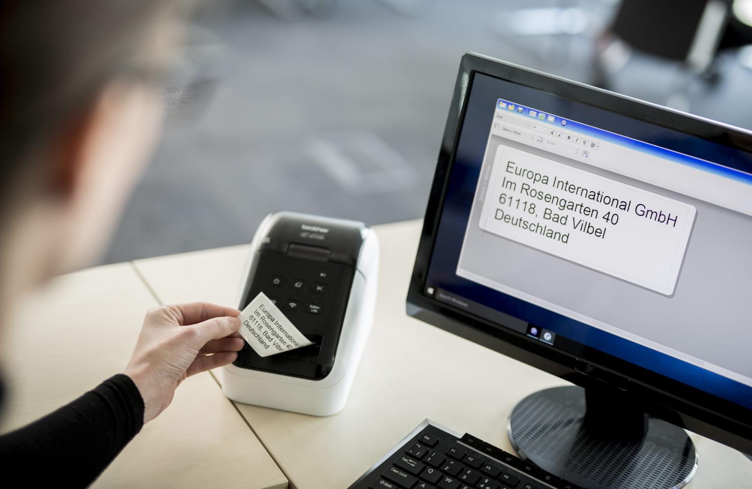 Uredski radnik uklanja ispisanu naljepnicu s QL pisača naljepnica