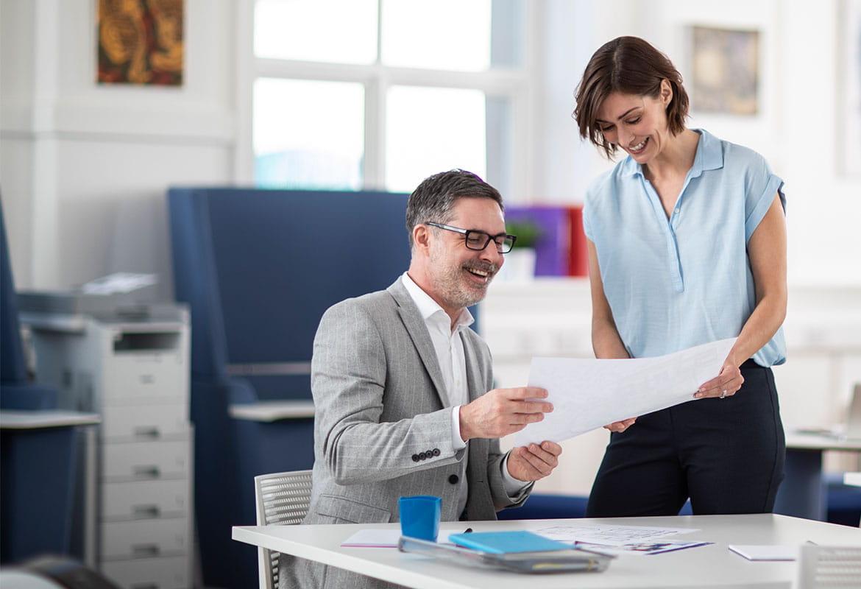 Muškarac i žena u uredu razgovaraju o dokumentu, crno-bijeli laserski pisač na ladicama u tornju u pozadini