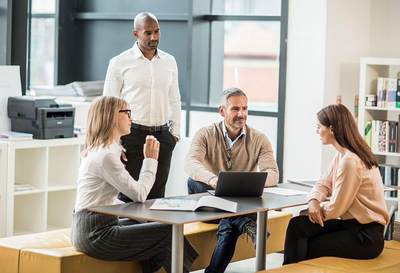 Skupina ljudi u uredu s crno-bijelim laserskim pisačem u pozadini
