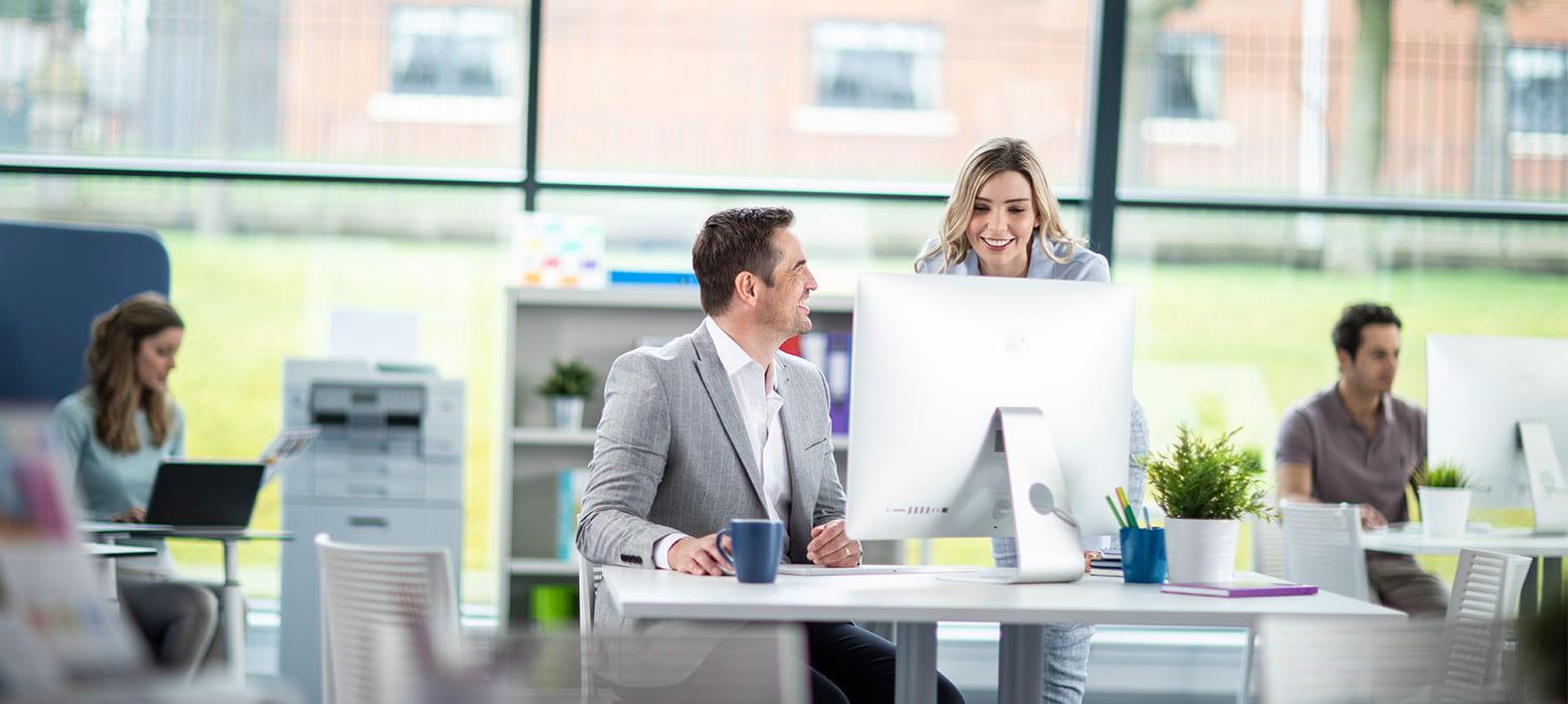 Muškarac sjedi kod stolnog računalo i razgovara sa ženom duge plave kose; u pozadini ljudi rade na prijenosnim računalima, pisači, šalice, biljke, stolice, ured