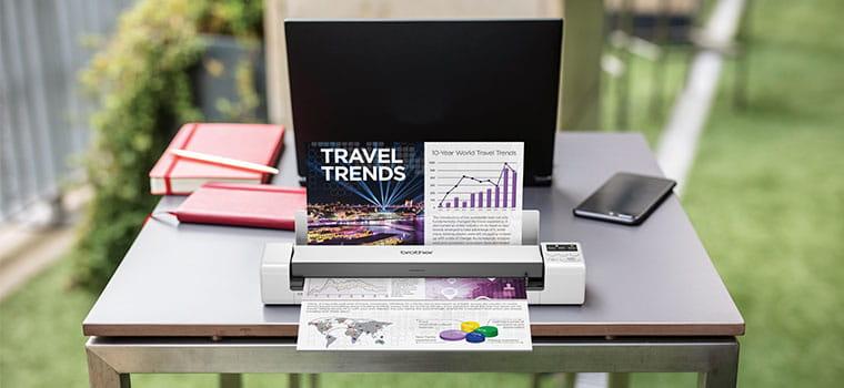 Brother DS-620 mobilni skener dokumenata skenira dokument u boji na stolu, laptop, narančasta bilježnica, mobitel, trava, na otvorenom