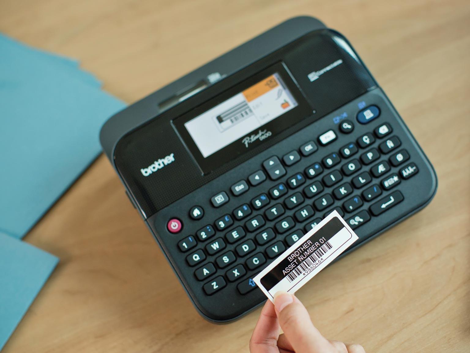 Brother P-touch D600 pisač naljepnica s rukom koja drži naljepnicu za označavanje imovine
