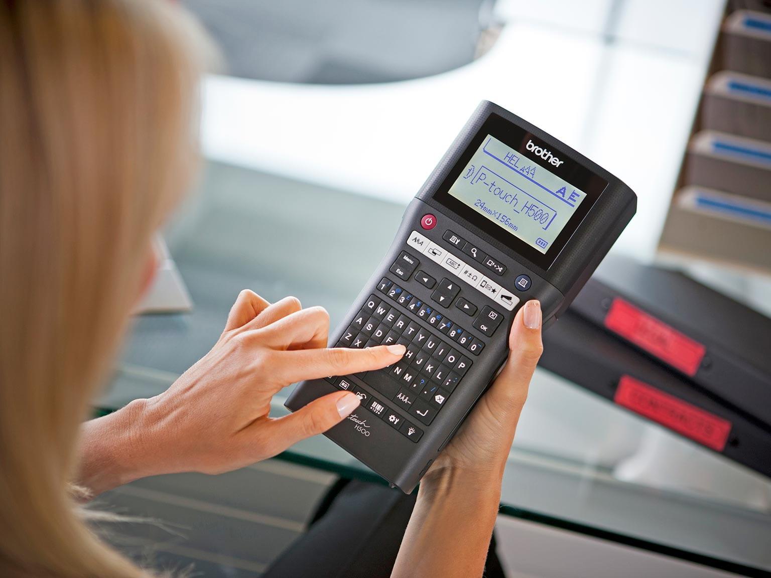 P-touch H500 pisač naljepnica ispisuje naljepnicu dok ga drži u ruci upravitelj objekta
