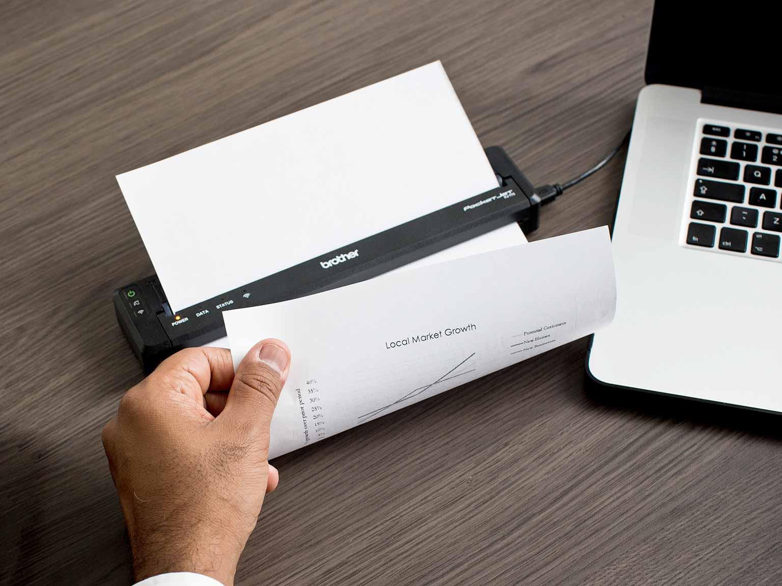 Prodavač ispisuje stranicu A4 na mobilnom pisaču serije Brother PJ
