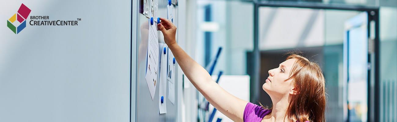 žena pričvršćuje list na zid u uredu