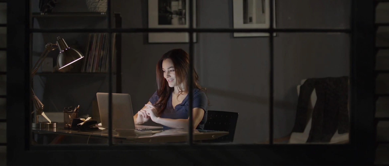 Žena u večernjim satima sjedi za stolom s prijenosnim računalom