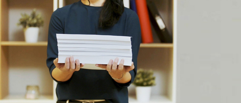 Žena drži hrpu papira