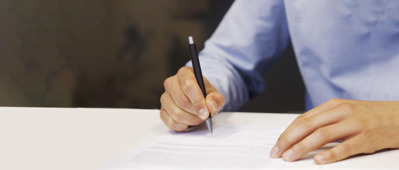 Muškarac u plavoj košulji podpisuje dokument