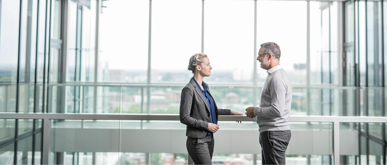 Poslovni muškarac i žena se sretnu na balkonu ureda
