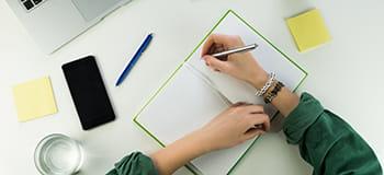 pisanje u bilježnicu na stolu s vidljivim mobilnim telefonom
