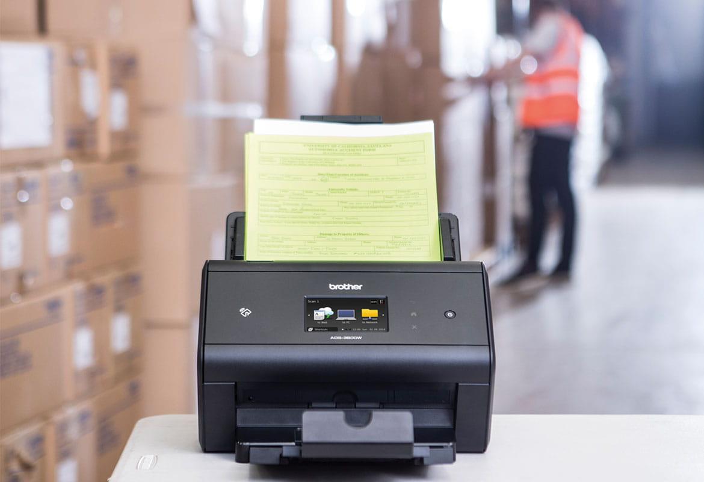Brother ADS-3600W stolni skener arhivira otpremnice u skladištu, kutije, muškarac u signalnom prsluku
