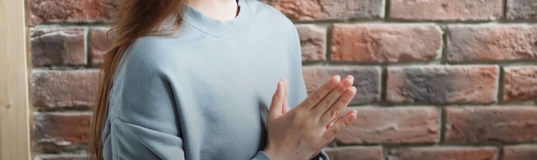 Žena sjedi i drži sklopljene dlanove