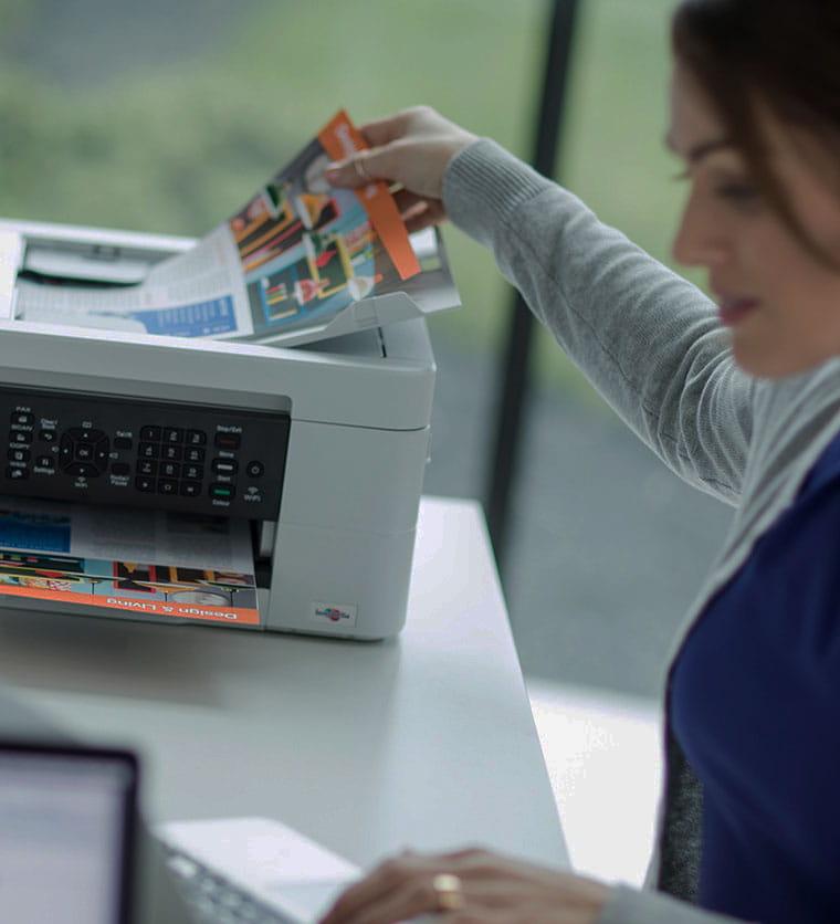 Žena sjedi za stolom i uzima dokument iz pisača