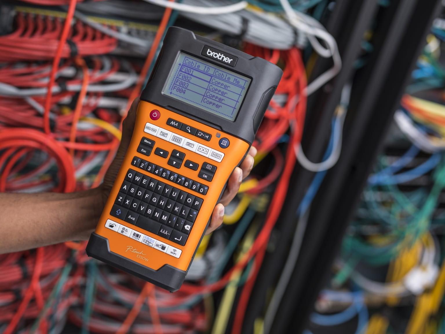 PT-E550W pisač naljepnica u ruci ispred mrežnih kabela