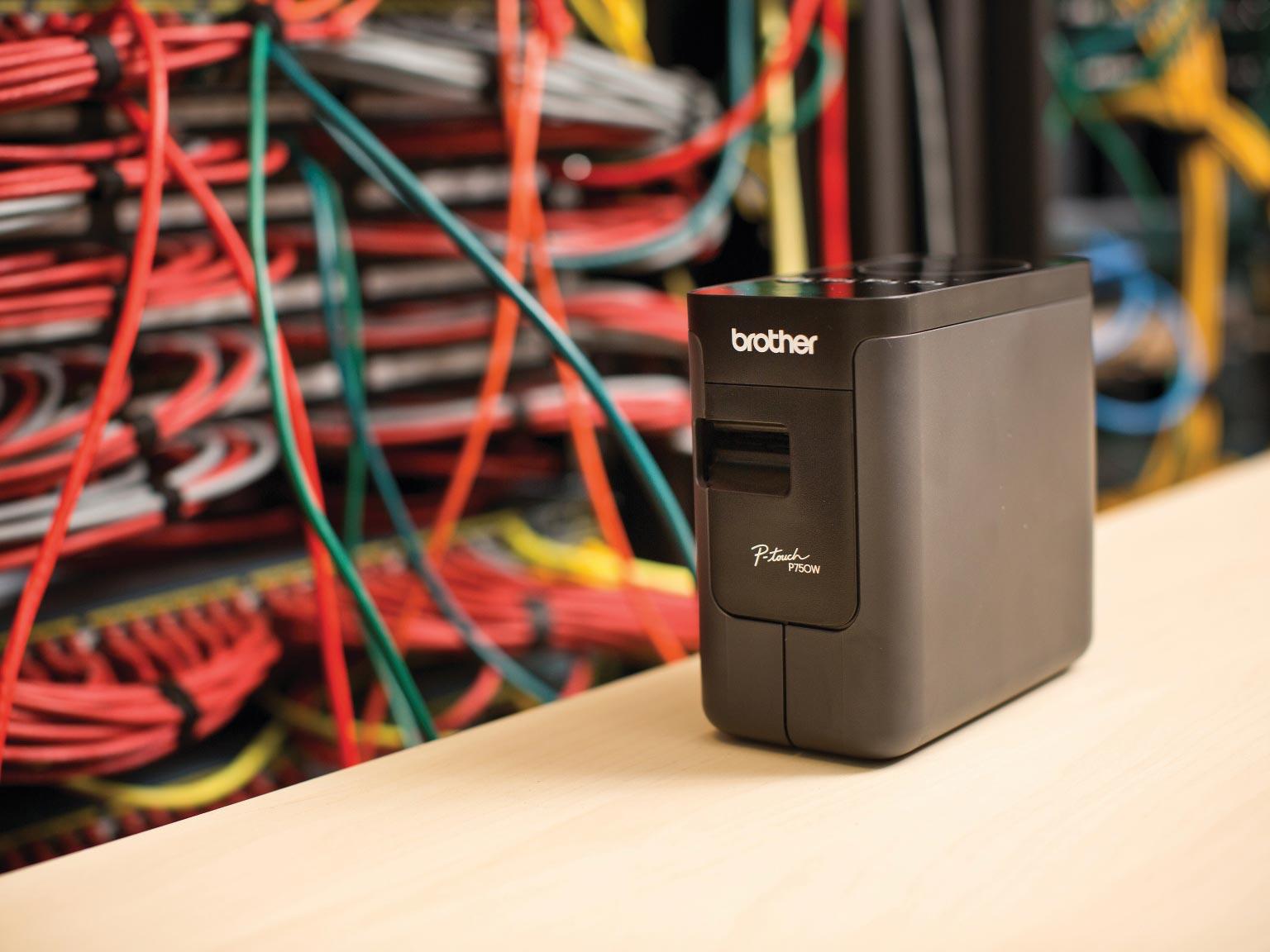 PT-P750TDI  pisač naljepnica na stolu ispred mrežnih kabela