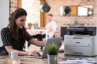 Tamnokosa žena sjedi za stolom s pisačem i prijenosnim računalom