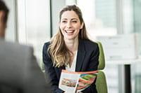 Žena sjedi u uredu s pisačem u boji u pozadini i smiješi se