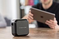 Muškarac s tabletom i P-touch Cube Plus koji ima bateriju