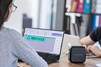 Žena s naočalima izrađuje naljepnice na P-touch Cube Plus putem računala