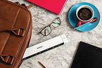 Brother DS-640 mobilni skener dokumenata, naočale, kava, kožna torba za laptop, olovka, tablet, ružičasta bilježnica