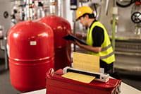 Inženjer u žutoj kacigi i signalnom prsluku, kleči s mapom s kopčom u ruci, Brother DSmobile DS-940DW mobilni skener dokumenata u strojarnici