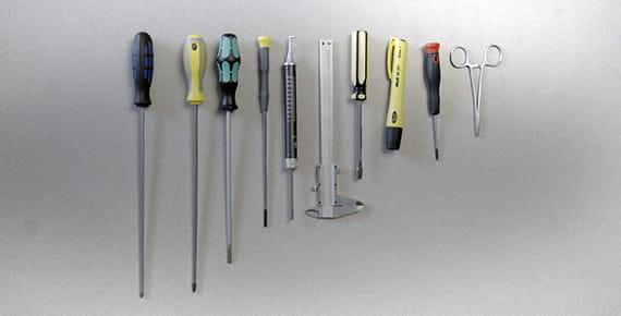 Izvijači, škarje in drugo orodje, pritrjeni na steno